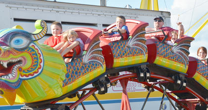 Teenagers and adults alike enjoy riding the midway rides, like this children's roller coaster, at the fair.
