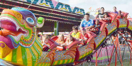 Fairgoers smile as they ride a roller coaster.