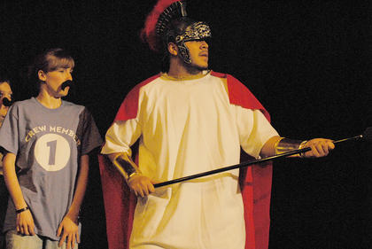 Odysseus, played by Ozzie Delgado, battles an enemy. At left is Crew Member 1, portrayed by Catherine Gray.