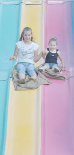 Selena Smith, at left, and Susan Davis, both of Lebanon, hold hands as they slide down the slide at the fair.