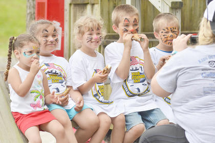Area children, who took advantage of free face painting, take a photo together after learning how to make s'mores.