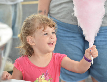Stephanie McQueary, 3, of Campbellsville, smiles as she prepares to take a bit of cotton candy at the Family Fun Zone.