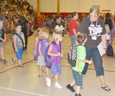 First-grade teacher Melissa Collison leads her students to their classroom.