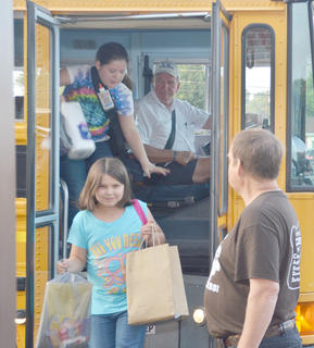 Mike Williams greets students as they get off the bus at TCES. In front is Leslie Green.