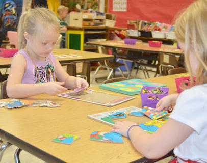 Kindergartener Gabby Tuck works a puzzle with her new classmates.