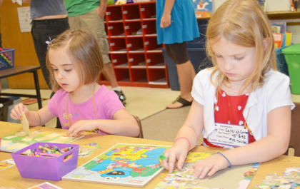 Kindergarten students Anna Floyd, at left, and Calleigh Carter work puzzles together before school starts.