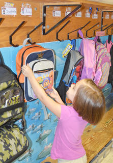 Kindergartener Anna Floyd finds the hook that will hold her backpack.