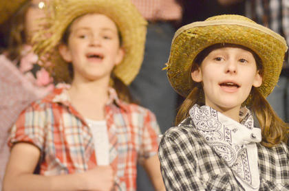 Choir members Chloe Hafley, at left, and Catherine Allen sing about the Wild West.