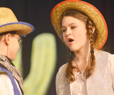 Miranda Oliver, portraying sharpshooter Annie Oakley, shares a scene with Isaac Rogers as Buffalo Bill.