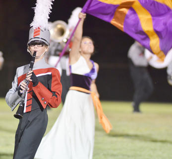 Clarinet player Hannah Bertram plays with the TCHS band while color guard member Allison Miller twirls her flag.