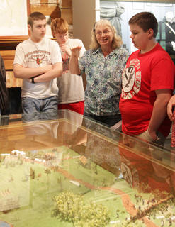 Cheryl Tillery of Tebbs Bend Battlefield Association talks to students as they look at a model of the Tebbs Bend Battlefield inside the Atkinson-Griffin House.
