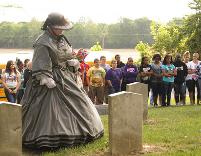 Connie Morris, a Civil War re-enactor from Fort Duffield in West Point, Ky., places a flower at the grave of a Confederate soldier as Campbellsville students look on.