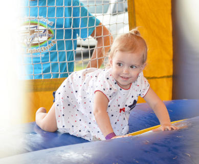 Tenley Dobson, 23 months, of Campbellsville, smiles at her mother and grandmother as she tests out a bouncy house at the Family Fun Zone.