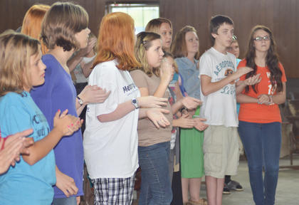 Children clap to the music as NorthBound, a contemporary praise and worship band from Russell Springs, performs. The band's performance was part of youth night.