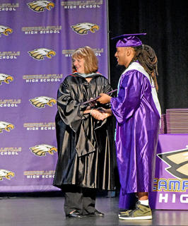 Angie Johnson, Campbellsville Independent Schools board member, hands Ceondre Barnett his diploma.