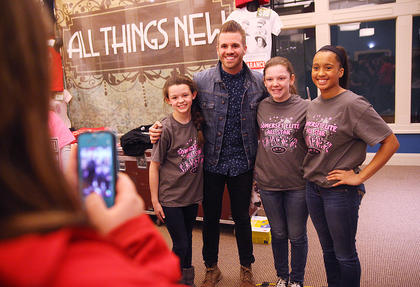 Garrett Hornbuckle, lead singer of the band All Things New, poses for a photo with some fans after the show.