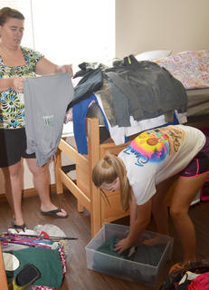Aleesha Ailiff of Frankfort organizes her clothing in her dorm room at CU's new village, with some help from her mom, Janice Newton.