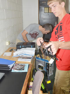 Devin Mayne of Somerset works to organize his desk in his dorm room, with some help from his father, Robert.