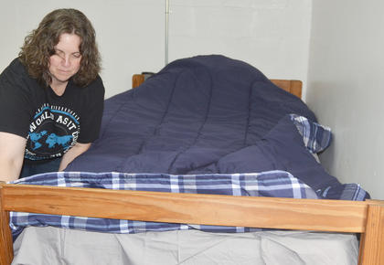 Cathy Mayne of Somerset makes her son Devin's bed as he moves into his dorm room.