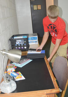 Devin Mayne of Somerset works to organize his desk in his dorm room.