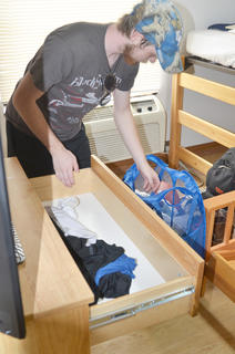 Drew Page of Paris, a senior at CU, places clothing in a drawer in his dorm room.