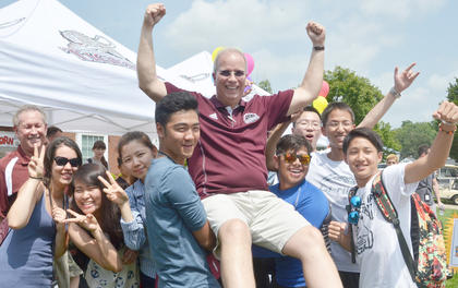 International students lift CU President Dr. Michael Carter as they pose for a photo with him.