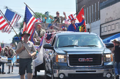 Members of Cub Scout Pack 777 and Boy Scout Troop 616 participate in the Fourth of July parade, providing one of the many patriotic floats.