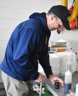 Firefighter Anthony Beard prepares cups of syrup at last week's Pancake Breakfast