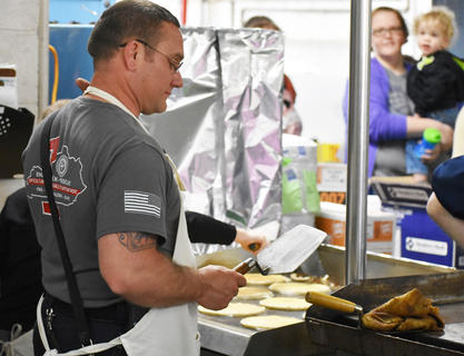 Firefighter Keith Bricken flips pancakes at the annual Pancake Breakfast.