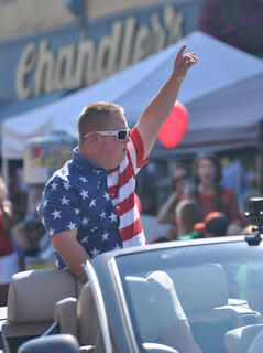 Parade Grand Marshal Brennan Wheatley celebrates as he rides in the Fourth of July parade.