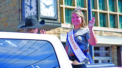 Miss Campbellsville Fourth of July Callie Jo McCubbin smiles and waves to the crowd Thursday.