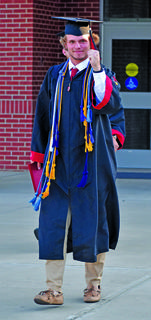 Taylor County graduate Cameron Kosid pumps his fist as he walks out the front door of the school following Friday's ceremony at Citizens Bank Arena.