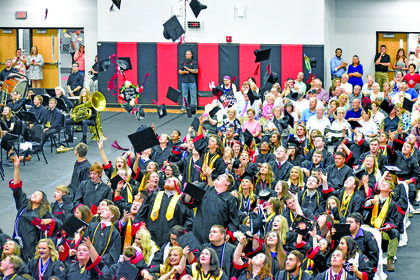 Graduates throw their caps at the conclusion of Friday's graduation ceremony.