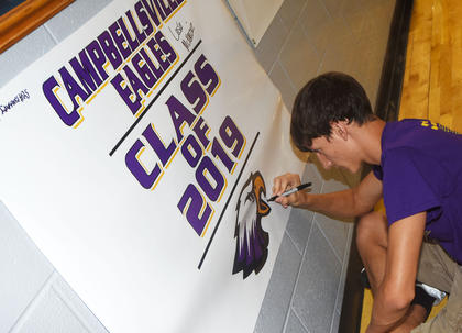 CHS senior Evan McAninch signs a Class of 2019 banner at project graduation.
