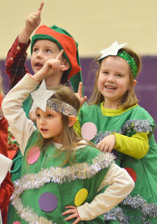 """They're counting down the days until the man in red comes to visit. Campbellsville Elementary School kindergarteners presented a """"Countdown to Christmas"""" musical on Monday, Dec. 9, for a full house of parents and community members. Students in Melanie Adams', Leanna Cundiff's, Chanci Patterson's, Linda Ward's and Lisa Wiseman's classes participated. Above, Madie Gebler, in front, and Tye Rhodes and Maylee Wilds dance to """"This Little Light of Mine"""" as they are dressed in Christmas costumes."""