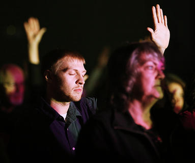 """A fan raises his hand in praise during a song by Sanctus Real as the """"Hands of God"""" tour stopped in Campbellsville."""