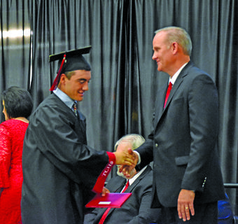 Taylor County graduate D.J. Goodin, left, shakes hands with TCHS Principal Jon Hall after receiving his diploma Friday night.