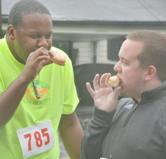 DeMarcus Compton, at left, and Cole Torbert eat donuts as they finish half of their 1-mile walk.