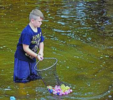 Quinton Anderson, 11, of Greensburg, kindly offered to help collect ducks from Trace Creek after the 15th annual Duck Derby hosted by the Central Kentucky News-Journal in collaboration with the Campbellsville Rotary Club. Duck 105, the first place winner, belonged to Jeanne Smith.