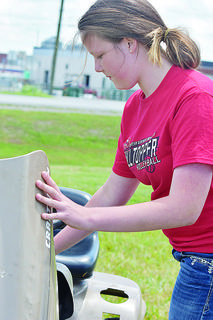 Eleven-year-old Samantha Akridge does her pre-contest safety checks prior to the lawn tractor driving contest. She was the reserve champion for the junior division of that competition and the tractor driving contest.