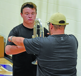Cameron Johnson, band director at CHSl, helps senior Conner Riley with his posture.