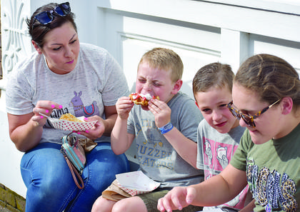 From left, Amber Pegram; Braddock Pegram, 7; Branston Pegram, 5; and Liv Pegram, 10, enjoy some of the treats that were sold at the event.