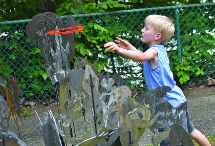 Emmett Davenport, 5, of Adair County, creates his own version of a ring toss game.