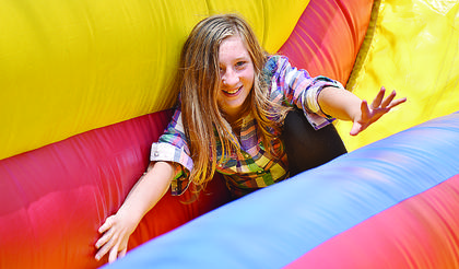 Aryona Hess, 11, of Casey County, braces herself while having fun on the inflatable slide.