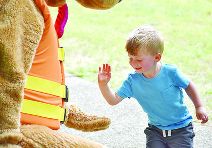 Tanner Phillips, 2, gives a high five to Bobber the Water Safety Dog.