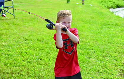 Kingston Mitchell, 4, of Campbellsville, goes for a big windup as he prepares to cast his fishing rod.