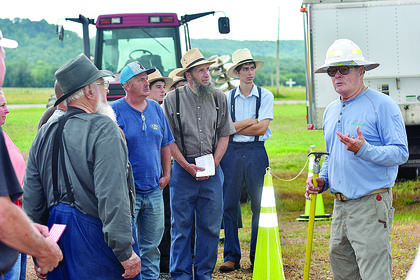 A group listens to safety tips around power lines from Clarence Greene, director of safety and loss control at the Kentucky Association of Electric Co-Op.