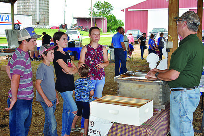 From left, Johnny Murphy, 15; Matthew Lowe, 10; Betty Lowe, 14; Kevin Lowe, 4; and Rebecca Lowe, 16, listen to a presentation from Green River Beekeepers Vice President Michael Pellittiere.