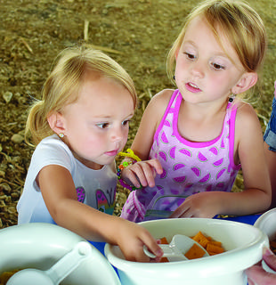 Addison Curry, 2, and Carleigh Curry, 4, make their own bag of trail mix at the Taylor County 4-H station.