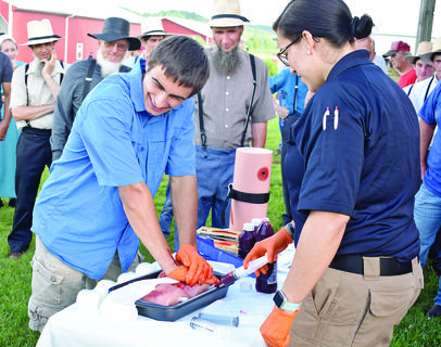 """Wes Oliver (left), 17, was chosen as a volunteer to demonstrate how the """"Stop the Bleed"""" method works. He is shown how to keep pressure on the wound by EMS Paramedic Renee Blackaby."""